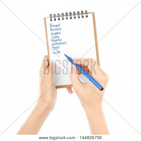 Hands holding pen and notepad with shopping list on white background