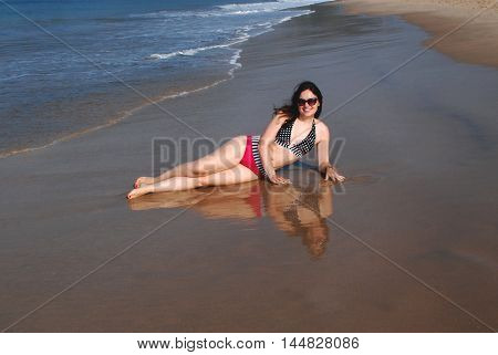 Happy beautiful girl in a bikini is lying on the beach at the water's edge and she is mirrored in the water on the wet sand