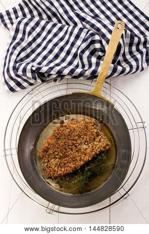 grilled scottish kipper coated with organic oatmeal and thyme in a pan