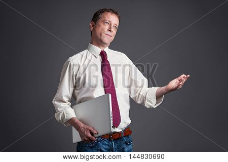 A middle age man standing with a laptop and feeling upset