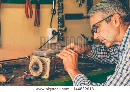 Man mechanic worker in his workshop and repairing motor. Small business.