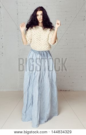 Girl in knitted sweaters with disheveled hair and a wonderful tender surprised. Model girl in studio with loose wild hair. Beautiful fluffy long blue skirt and raises hands to her hair poster