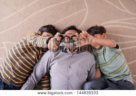 Indian father and sons lying on floor and taking selfie