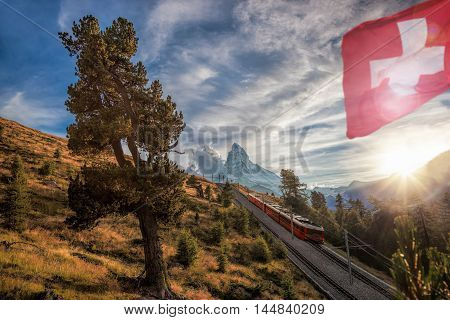 Matterhorn Peak With A Train And Flag Of Switzerland In Swiss Alps