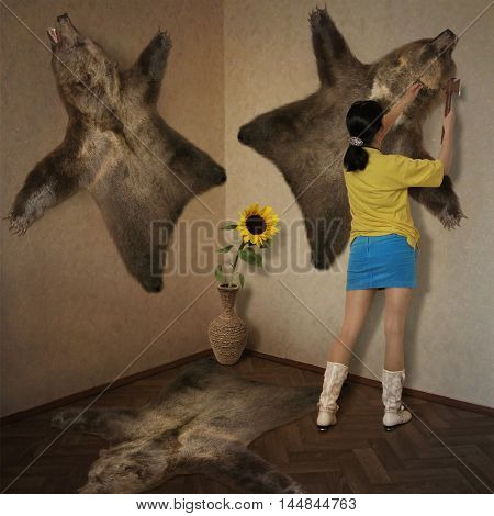A girl is fixing a bearskin to a wall.