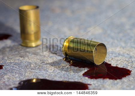 Two pieces of handgun brass on concrete with blood