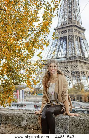 Elegant Woman Sitting On Parapet On Embankment Near Eiffel Tower