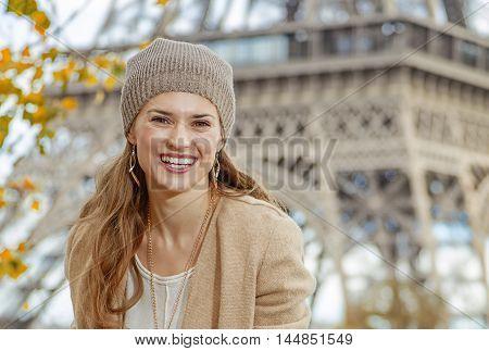 Tourist Woman Sitting On Parapet On Embankment Near Eiffel Tower