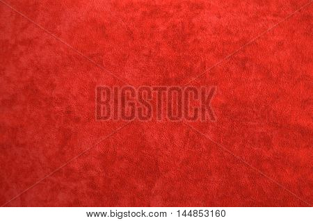 Background from a red perfect suede fabric. Velvet texture.