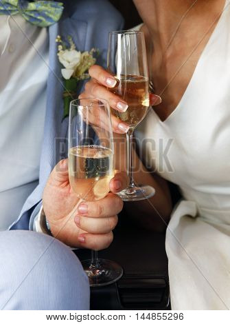 Glass of champagne in a hands of the groom and bride