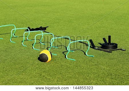 Medicine ball, banana hurdles and weighted sled on a green turf field