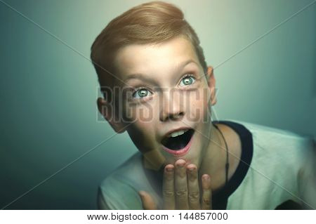 Surprised blond happy teenage boy with stylish haircut and bright eyes.