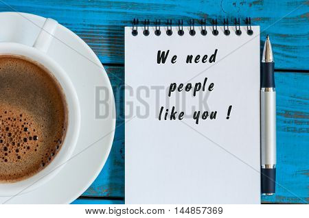 WE NEED PEOPLE LIKE YOU message on the notepad at workplace with cup of morning coffee. Hiring concept.