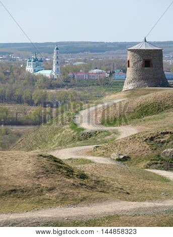 Tower of ancient Bulgar fortress on a high cliff on the banks of the Kama River sunny spring day