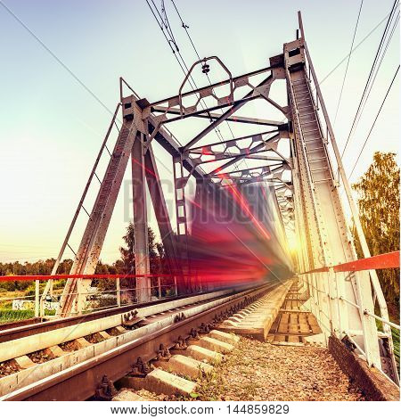 Highspeed train moves fast on the bridge at sunsset.