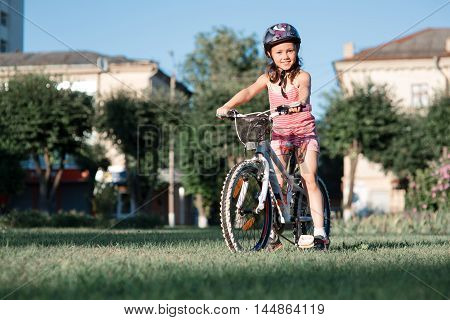 happy child girl riding bicycle in summer sunset in the park. Active kids