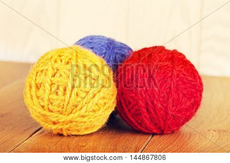 colorful yarn balls lying on wooden background