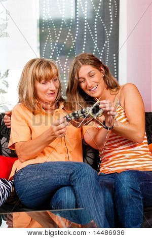 Woman teaching her daughter knitting in her living room