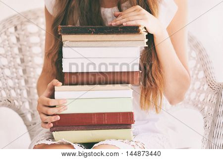 Woman holding stack of old books