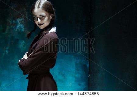 Halloween theme: Portrait of a young smiling girl in school uniform as killer woman against school board . The image in the style of Halloween and Addams family