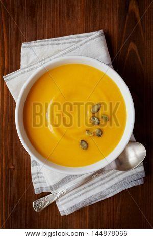 Fresh autumn pumpkin cream soup in bowl, dietary vegetable food, top view.