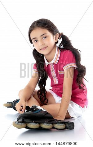Nice little girl of Eastern appearance in a pink shirt and white shorts . Long dark ponytails hair down below the shoulders. The girl puts on leg on roller skates . Sitting on the floor