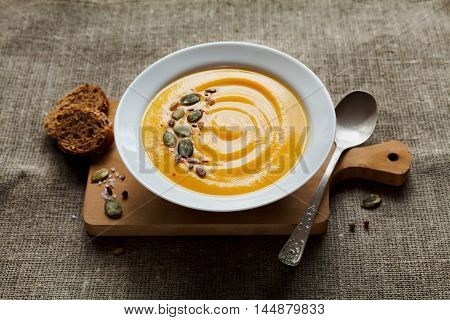Pumpkin soup with rye bread in white bowl. Dietary vegetable and healthy food. Rustic style.
