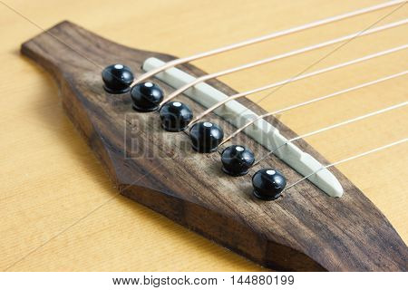 Still life photo by acoustic guitar bridge pins and saddle poster