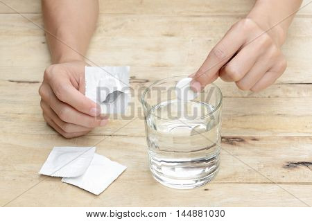 woman hand dropping effervescent tablet in a glass of water on wooden table