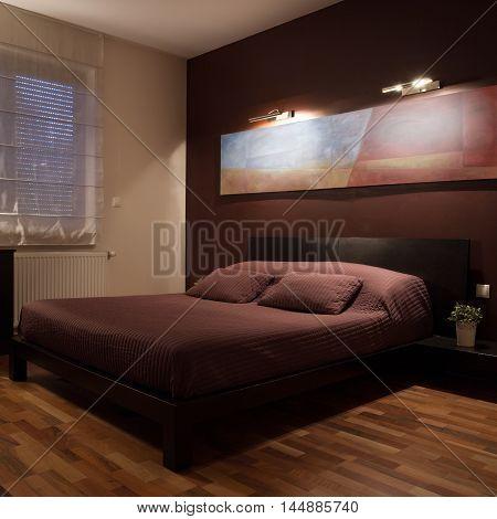 Big double bed in modest bedroom with wooden floor