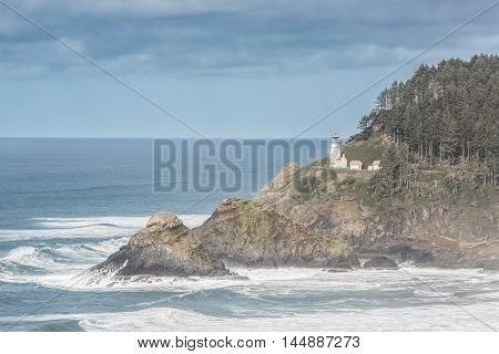 Coastal view of Heceta head lightstation in Yachats, Oregon with crashing waves and fog during storm clouds