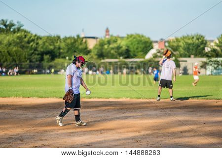Washington D.C., USA  - August 4, 2016: Happy, smiling people playing baseball on the National Mall with woman pitcher
