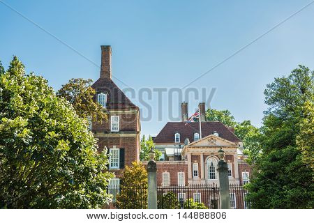 Washington, DC., USA - June 29, 2016: British Embassy in city with trees, gate and brick building with England flag