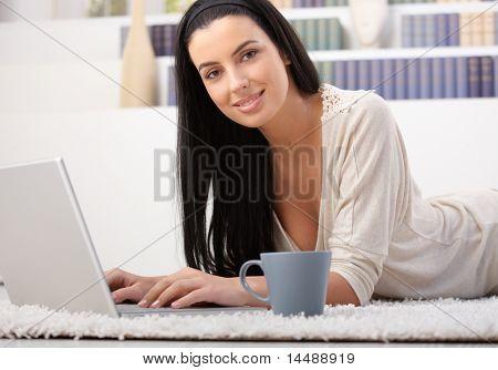 Attraktive Frau liegend auf Teppich mit Laptop-Computer zu Hause, beim Kaffee, lächelnd in die Kamera?