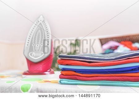 Iron and ironed clothes on an ironing board.