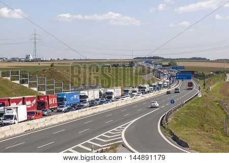 ASCHAFFENBURG GERMANY - AUG 17 2016: Trucks stuck on two right lanes because of a traffic jam caused by a construction site