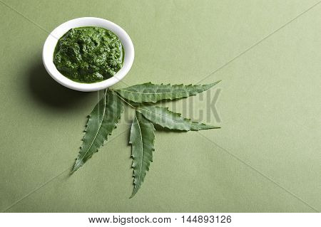 Medicinal Neem leaves with paste in bowl on green background