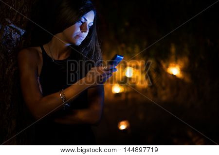 Woman with Smartphone in a Garden at Night