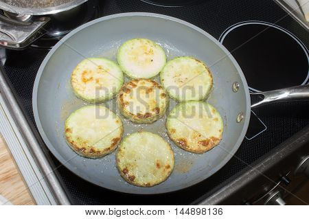 Sliced zucchini coated with eggs, flour and spices frying in a pan