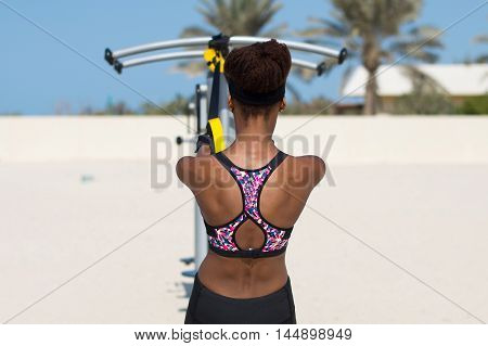 African female athlete doing exercises with suspension trainer at the sunny beach in Dubai