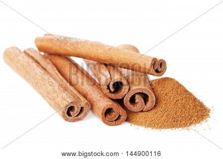 Closeup of cinnamon sticks and powder of ground cinnamon on white background. Isolated.