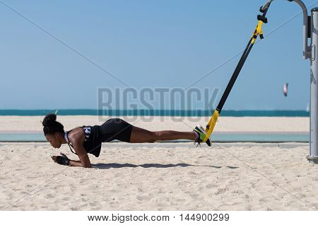 Female african doing difficult exercises using special ropes for suspension training. Sport activity at the beach in Dubai UAE