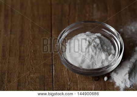 Baking soda, Sodium bicarbonate in glass bowl on wooden table. Copy space for text.