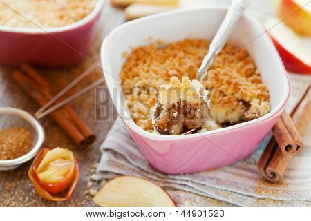 Apple crumble with cinnamon on rustic wooden table. Sweet dessert.