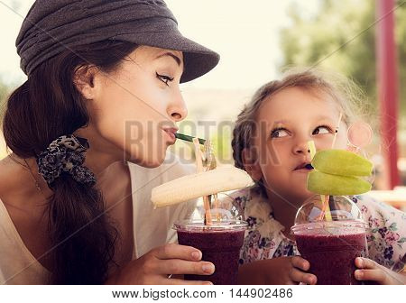 Friendly kid girl and fun emotional mother drinking berries smoothie juice together in street cafe and looking on each other. Closeup portrait