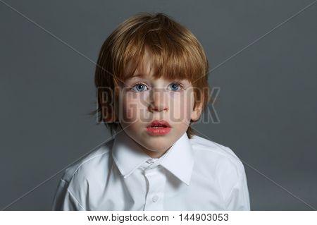 little serious boy portrait on dark background