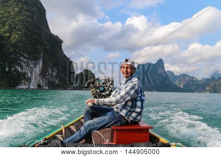 Suratthani Thailand - April 14 2015: Boat driver was on the back of long tail boat in speed floating on green water of dam called 'Ratchaprapha' in Suratthani Thailand.