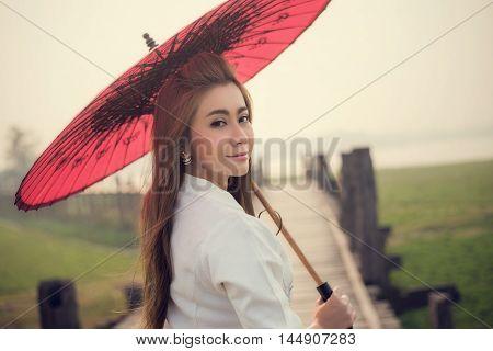 The Beautiful Burmese Woman In Myanmar Traditional Costume,with Red Umbrella Walking On Ubein Bridge