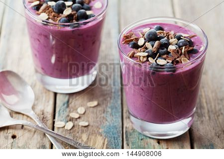 Healthy breakfast of smoothie dessert, yogurt or milkshake with frozen berry and oats, decorated grated chocolate on wooden vintage table.