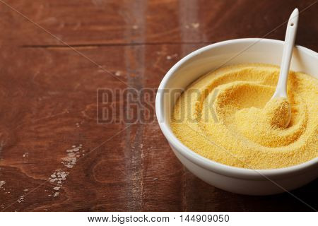 Corn meal or dry polenta in white bowl on vintage table. Copy space for text.